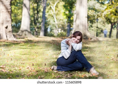 Young beautiful woman sitting on grass in central park, New york