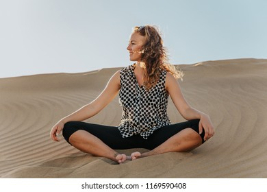 Young beautiful woman sitting on the desert sand and relaxing, meditation pose for inner peace