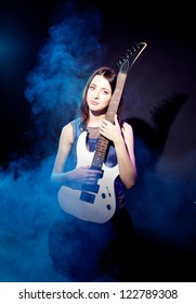 Young beautiful woman is sitting on stage with a  guitar . Fog on the stage