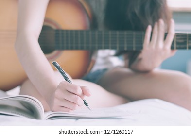 Young beautiful woman sitting on her bed in the bedroom holding guitar composing a song  and writing song in textbook ,musician, songwriter, composer concept