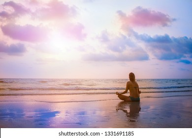 Young beautiful woman sitting on sunset sea beach and practicing zen yoga in lotus pose. Evening meditation with view on surrealistic sky and ocean. Reflection on wet sand.