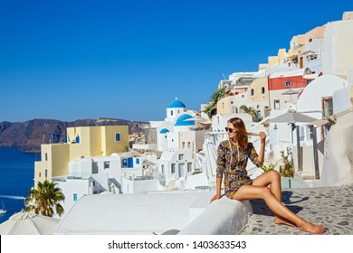Young beautiful woman sitting on a hill on the background of architecture, Santorini Island, Greece
