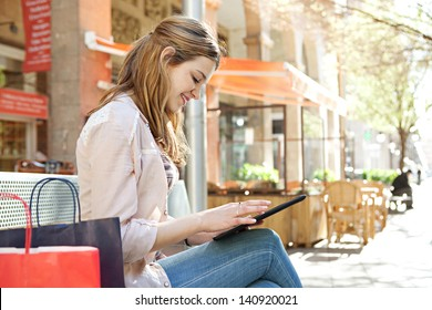Young beautiful woman sitting on a bench in a city center with her shopping bags during a sunny day, using a digital tablet pad near a coffee store bar, smiling.