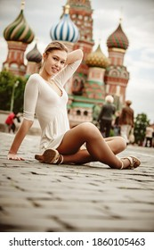 Young beautiful woman sitting on the cobblestones of Red Square in the background St. Basil's Cathedral. Moscow Russian Federation.