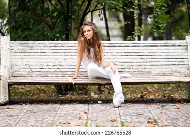 Young beautiful woman sitting on a bench in autumn park