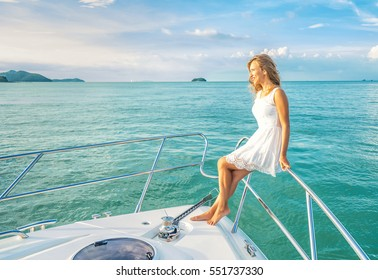 Young beautiful woman sitting on the yacht . Luxury travel on the yacht. Cruise vacation.