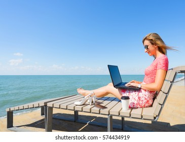 Young beautiful woman sitting on the beach chair with laptop , smartphone and shoes, and cup of coffee. Girl typing something on laptop.