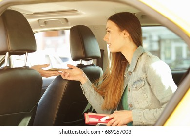 Young beautiful woman sitting on backseat and paying for taxi