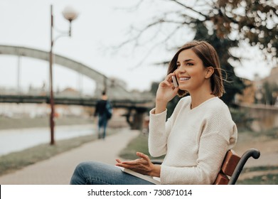 Young beautiful woman sitting on a bench in the city park and speaking on the phone.