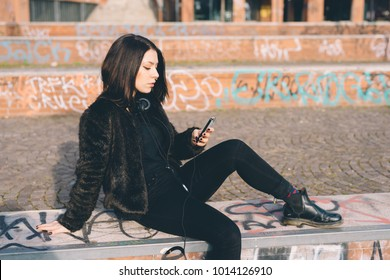 young beautiful woman sitting outdoor using smart phone - technology, social network, phubbing concept