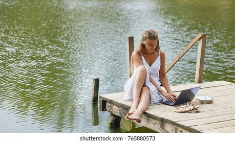 Young beautiful woman sitting at the pier and working on pc