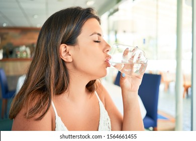 Young beautiful woman sitting at restaurant enjoying summer vacation drinking glass of water