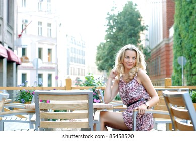 Young beautiful woman sitting in the summer cafe