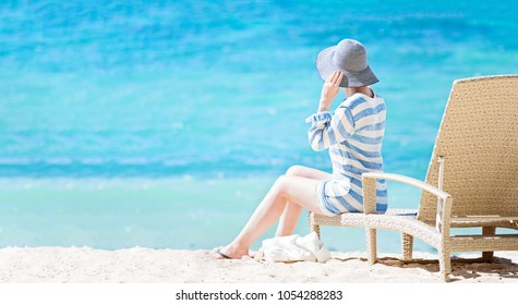 young beautiful woman sitting at sunbed at white sand beach enjoying sunshine, turquoise lagoon and tropical island vacation at fiji, copy space on left