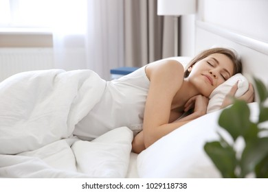 Young beautiful woman sleeping in bed at home
