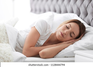 Young beautiful woman sleeping in bed at home. Early morning