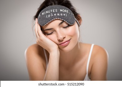 Young beautiful woman sleeping with eye mask on grey background. Portrait of brunette tired girl with eye mask for sleeping. Sleepy beauty woman resting on hand with closed eyes.