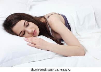 Young beautiful woman sleeping in her bed and relaxing in the morning.