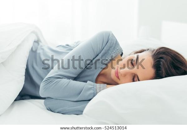 ベッドで寝て朝のリラックスした若い美人