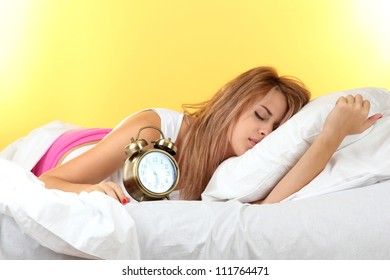young beautiful woman sleeping on bed with alarm clock on yellow background