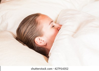 young beautiful woman sleeping on the bed under blanket
