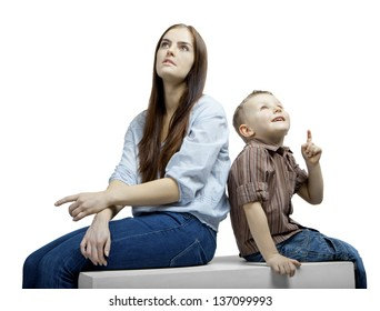 Young beautiful woman with a small boy sitting next to each other. They are talking and watching something.