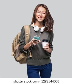 Young beautiful woman with smart phone. Smiling student girl going on a travel. Isolated on gray background