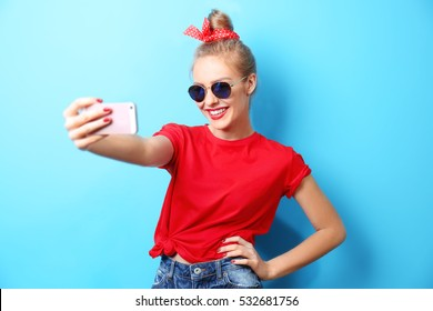 Young beautiful woman with smart phone on blue background