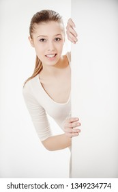 young beautiful woman smiles and looks out from behind the wall
