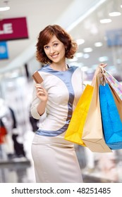 Young beautiful woman smiles in shop with bags and a credit card