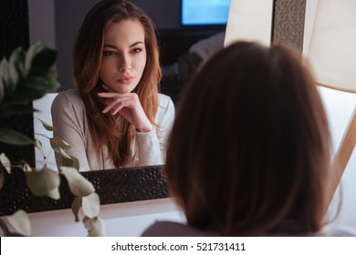 Young beautiful woman smiling to herself in mirror while sitting at bedroom