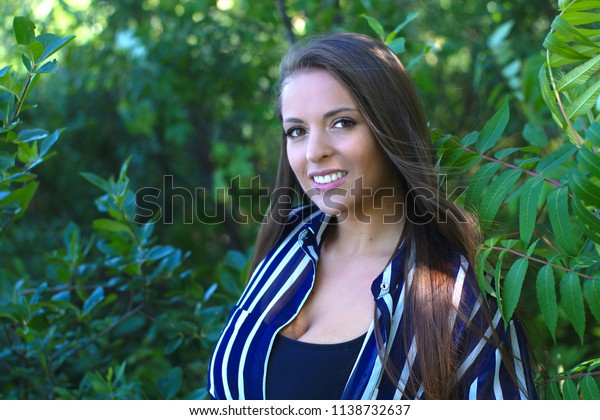 young beautiful woman smiling in nature forest sun light
