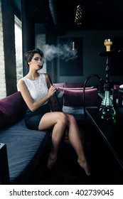 Young, beautiful woman smokes a hookah in cafe. It produces smoke from his mouth. Business style clothing. The pleasure of smoking.