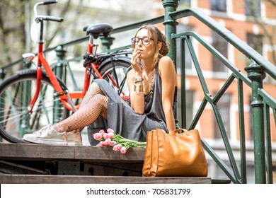 Young beautiful woman smoking a cigarette sitting with flowers and bicycle on the bridge in Amsterdam city