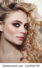 Young beautiful woman with smoky eye make-up and fancy curly hair