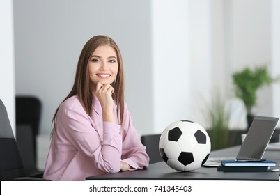 Young beautiful woman with soccer ball in office