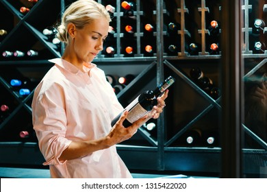Young beautiful woman sommelier tasting red wine in wine cellar. Image of woman with bottle of wine. happy blonde woman in store with wine.