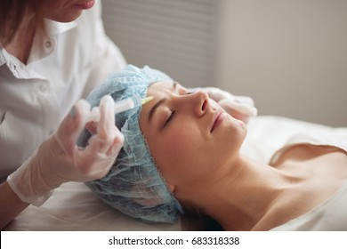 The young beautiful woman in a spa receiving facial treatment injections.