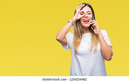 Young beautiful woman speaking calling using smartphone over isolated background with happy face smiling doing ok sign with hand on eye looking through fingers