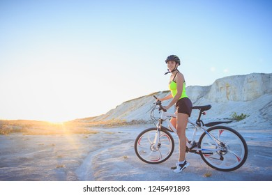 Young beautiful woman with a sport bike, blue sky background, blurred background