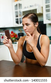Young beautiful  woman in sportswear with chocolate in the house kitchen. Healthy lifestyle.