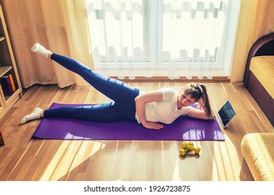 Young beautiful woman in sportswear doing fitness workout at home, side-lying hip abduction, lateral leg raises, lie on left side on floor mat and lift right leg up, tablet and dumbbells on floor