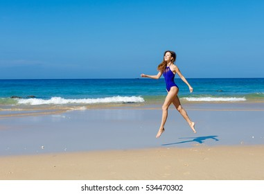 The young, beautiful woman the sportswoman in a bathing suit runs on the seashore.