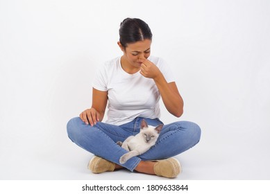Young beautiful woman standing against yellow background, holding her nose because of a bad smell coming out from the cat.