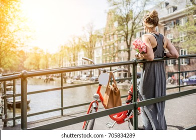 Young and beautiful woman standing with bicycle and flowers on the bridge over the water channel in Amsterdam city