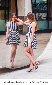 Young Beautiful Woman standing by metal mirror on street, looking down, thinking, wearing sleeveless, black and white striped short dress, sandals. Concept of self assured, self esteem, self checking.