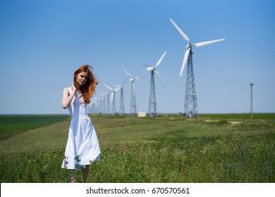 Young beautiful woman standing in the field, windmills.