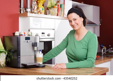 Young and beautiful woman standing in the kitchen beside a coffee machine
