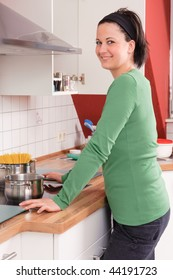 Young and beautiful woman standing in the kitchen