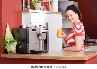 Young and beautiful woman standing in the kitchen with orange juice